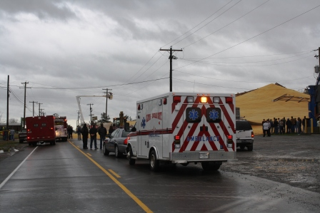 Emergency vehicles on the scene of 100 foot corn bin rupture