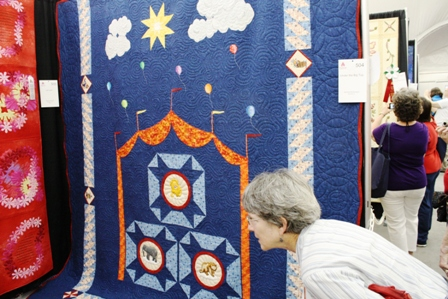 "Cherry Pyron looks at quilts. Blue quilt is called ""Circus"""
